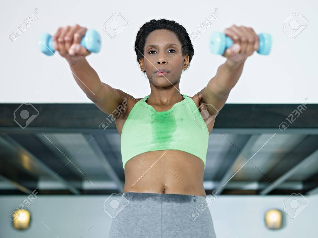 young african american woman in green sportswear doing weight lifting in fitness club. Horizontal shape, front view, waist up Stock Photo - 8843301