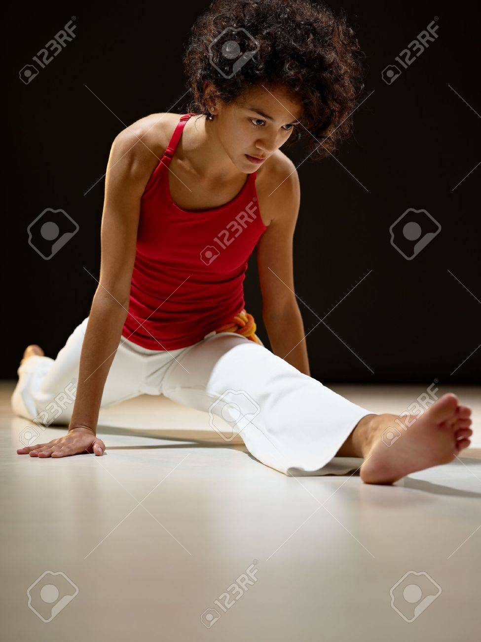 portrait of young adult latin american female doing yoga and stretching exercise in gym. Vertical shape, full length, front view, copy space Stock Photo - 8928992