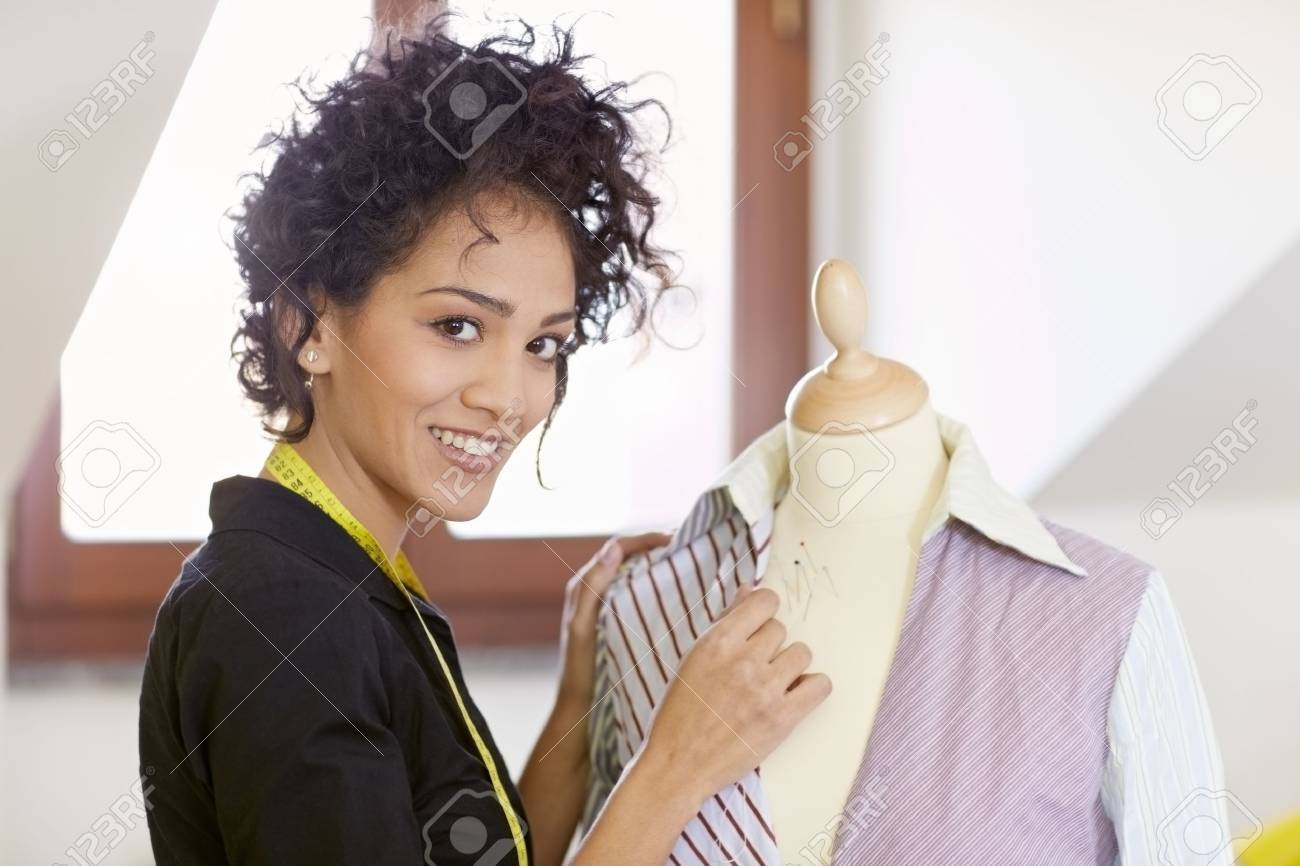 Young hispanic female dressmaker adjusting clothes on tailoring mannequin and smiling at camera. Horizontal shape, side view, waist up Stock Photo - 9124759