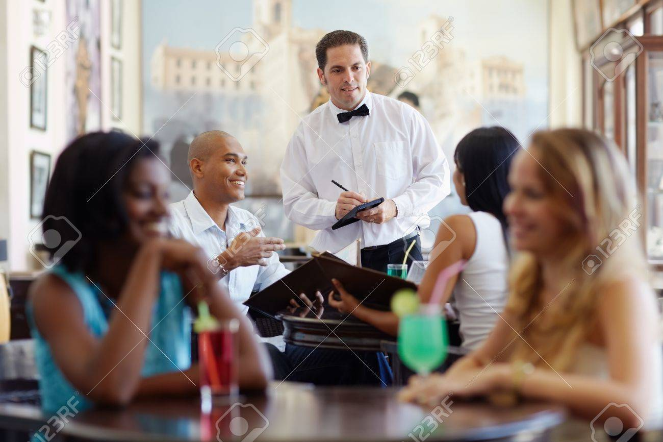 young adult hispanic couple dining out in restaurant and talking to waiter in bow tie. Horizontal shape, front view, waist up - 9626175
