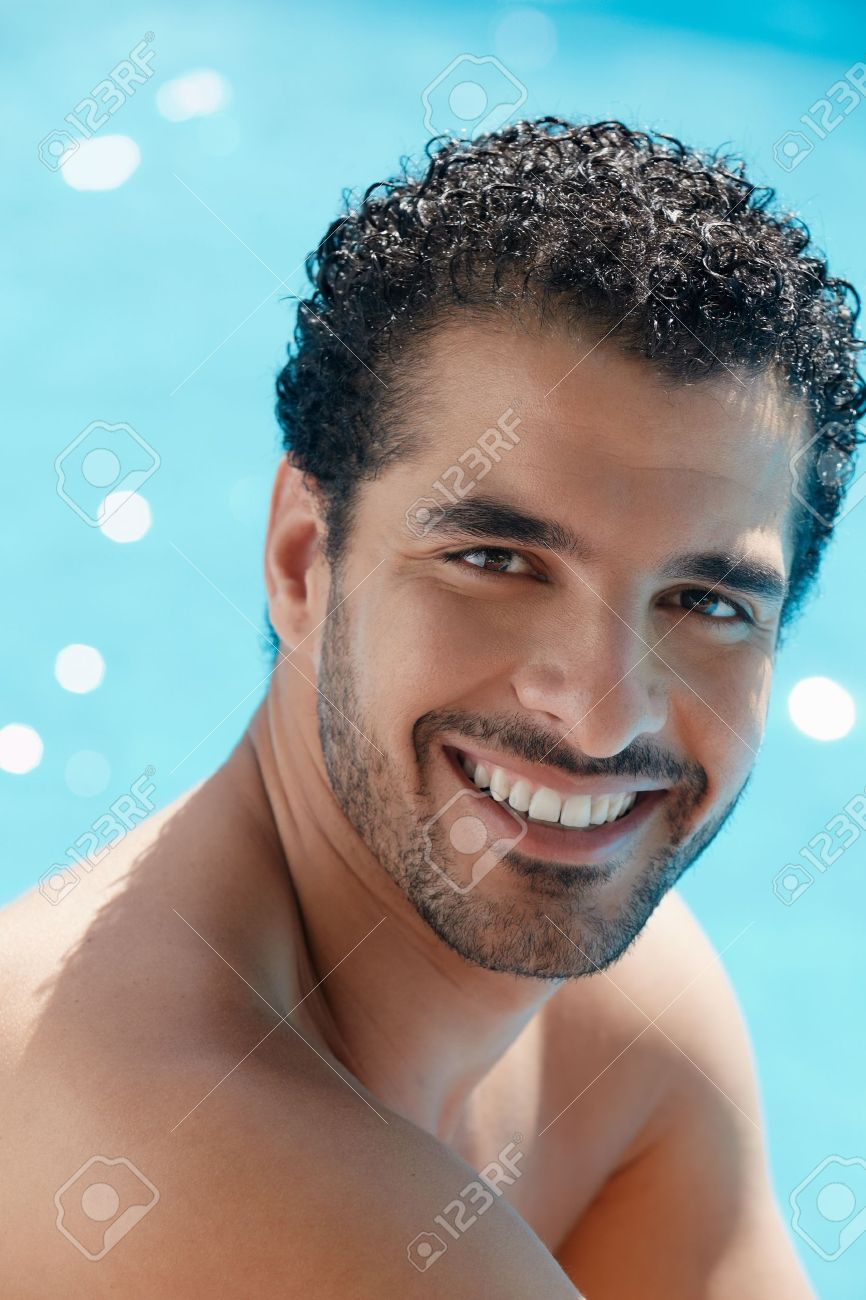 Handsome happy young hispanic man smiling and relaxing near hotel pool. Vertical shape, head and shoulders Stock Photo - 9663700