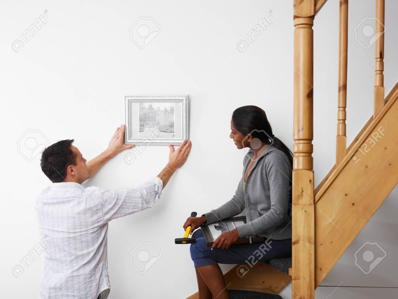 ミッド アダルト多民族カップル、壁に絵を掛けると笑みを浮かべてし ...