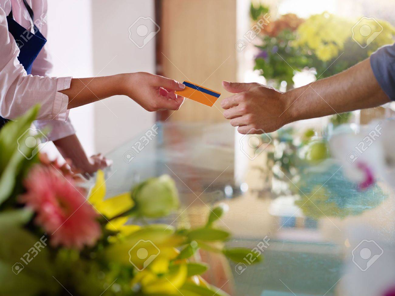 Young woman working as florist giving credit card to customer after purchase. Horizontal shape, closeup Stock Photo - 10684090