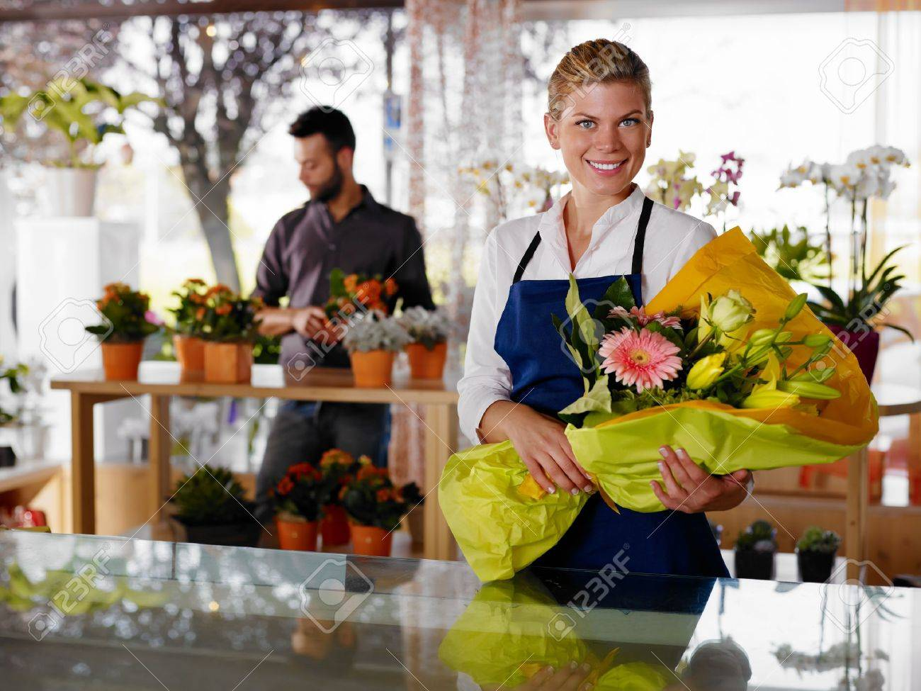female s assistant working as florist and holding bouquet female s assistant working as florist and holding bouquet customer in background horizontal shape