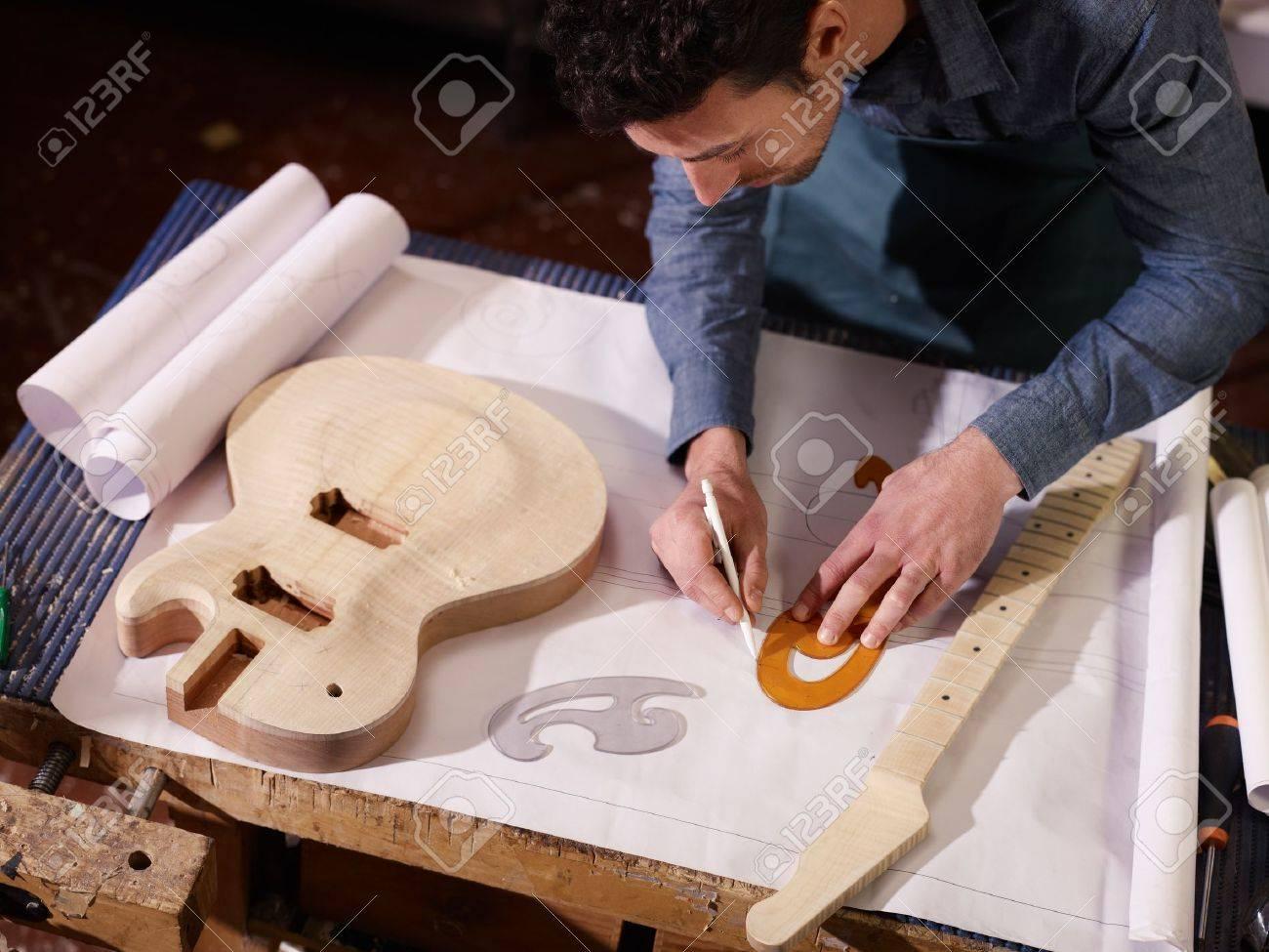 Mid adult man at work as craftsman in italian workshop with mid adult man at work as craftsman in italian workshop with guitars and blueprints drawing malvernweather Choice Image