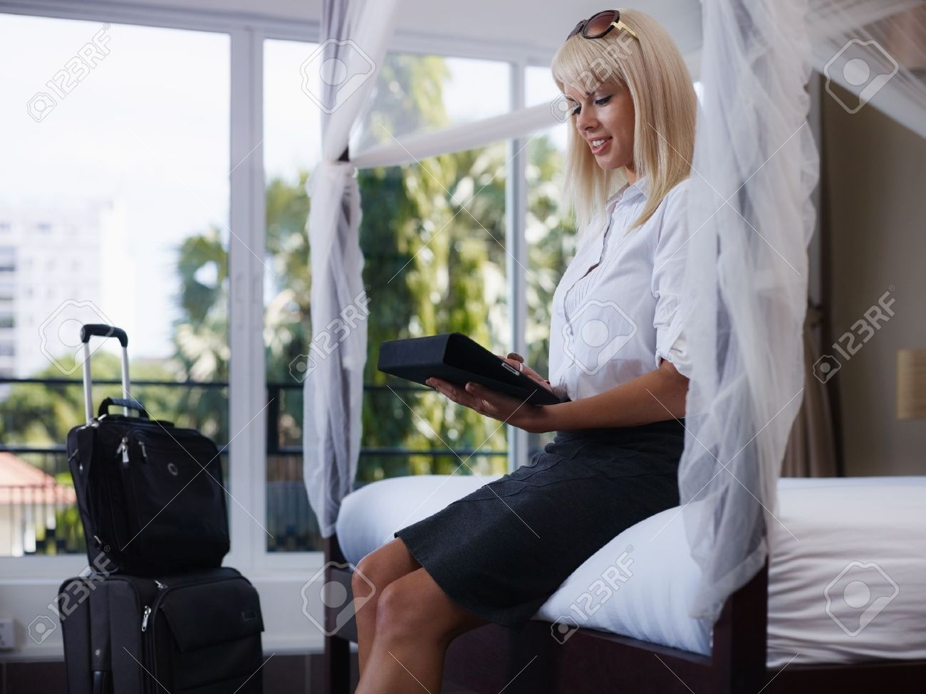 Mid adult caucasian businesswoman typing on tablet pc in hotel room during business travel. Side view, three quarter length Stock Photo - 11791625