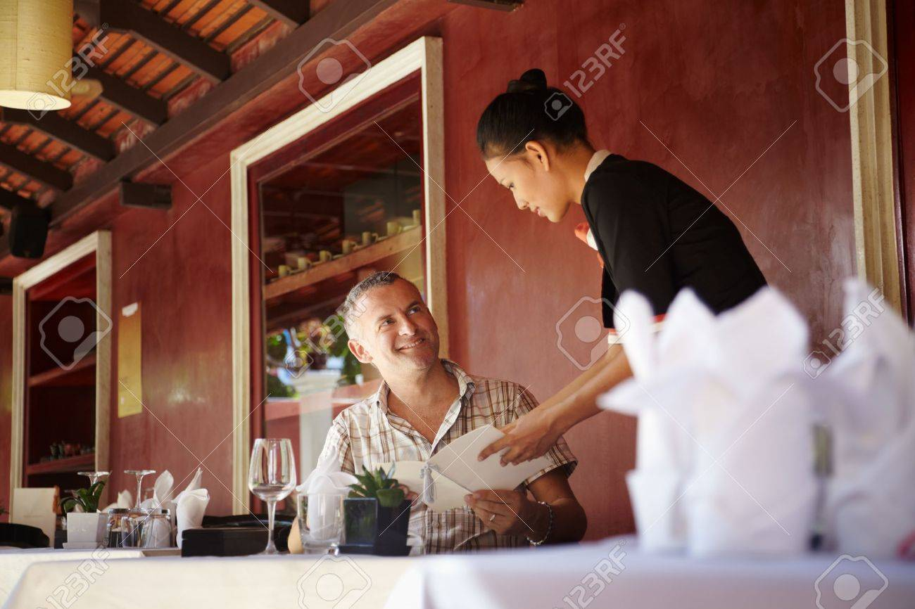 Attractive young asian woman working as waitress in exclusive restaurant and attending customer with menu Stock Photo - 12012562