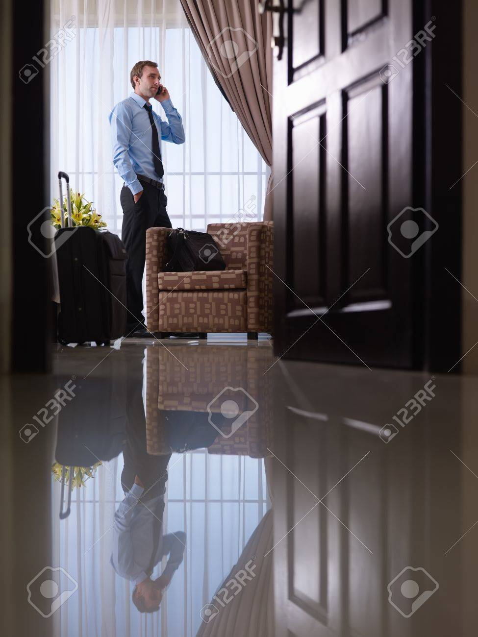 Caucasian mid adult businessman talking with mobile telephone in hotel room during business trip Stock Photo - 12055135