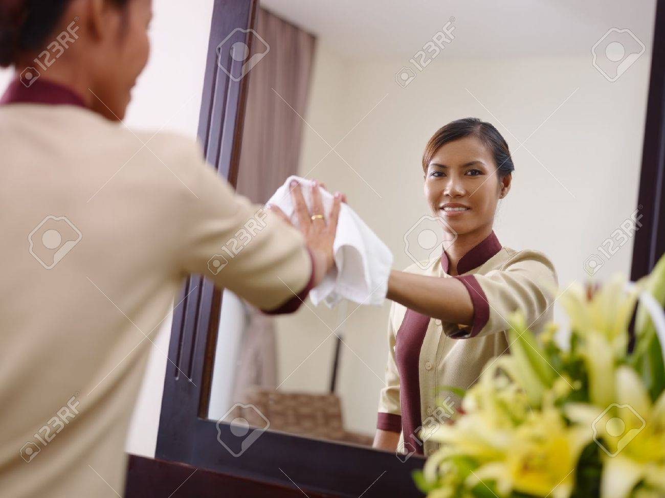 Portrait of happy Asian housekeeper at work in luxury hotel room and smiling at camera - 12055143