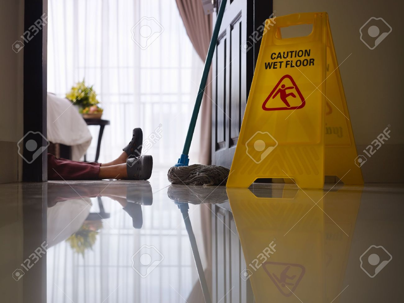 housemaid had accident at work while cleaning floor in hotel room. Side view, low angle Stock Photo - 12055144
