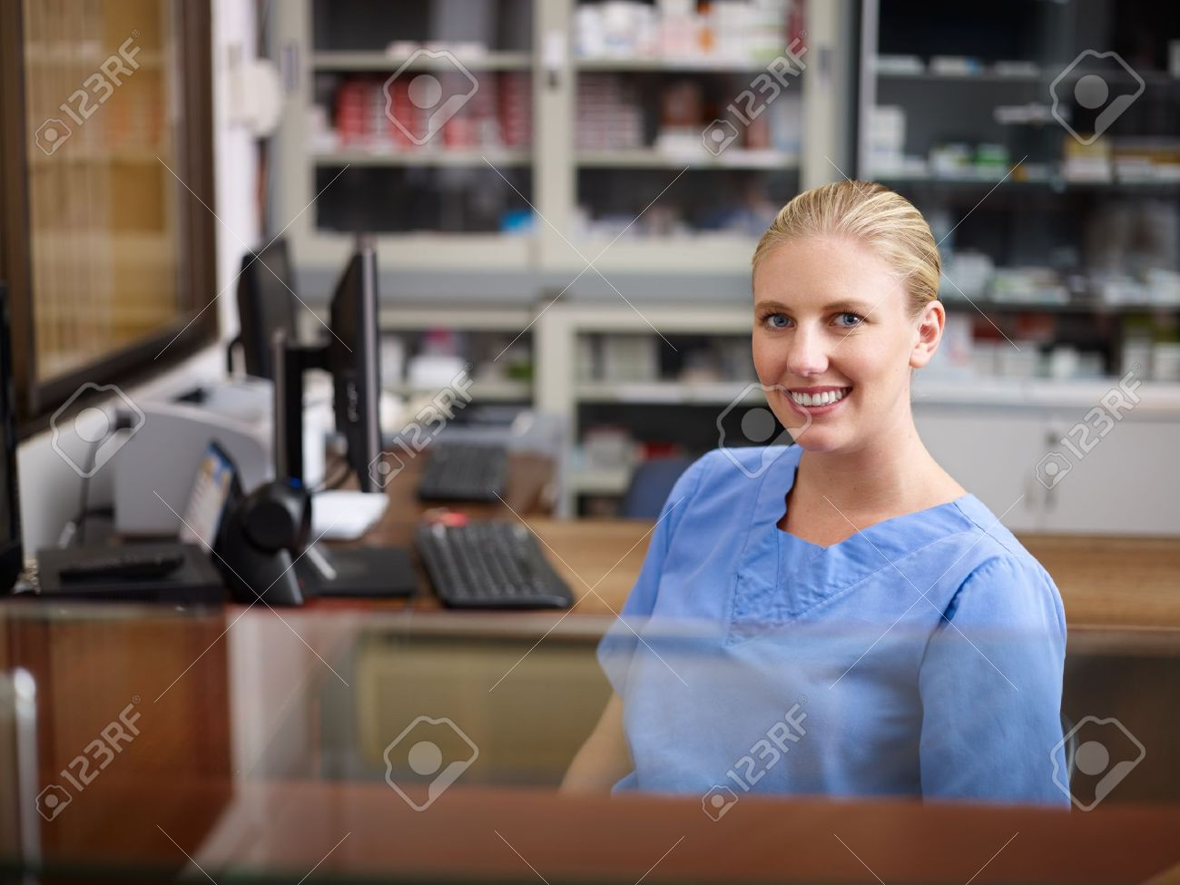 stock photo young woman at work as receptionist and nurse in hospital looking at camera