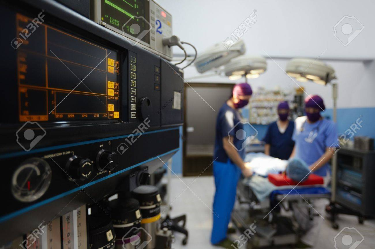 Team work with doctors, nurses, surgeons performing surgery on sick patient in hospital operation room. Focus on foreground Stock Photo - 12943214