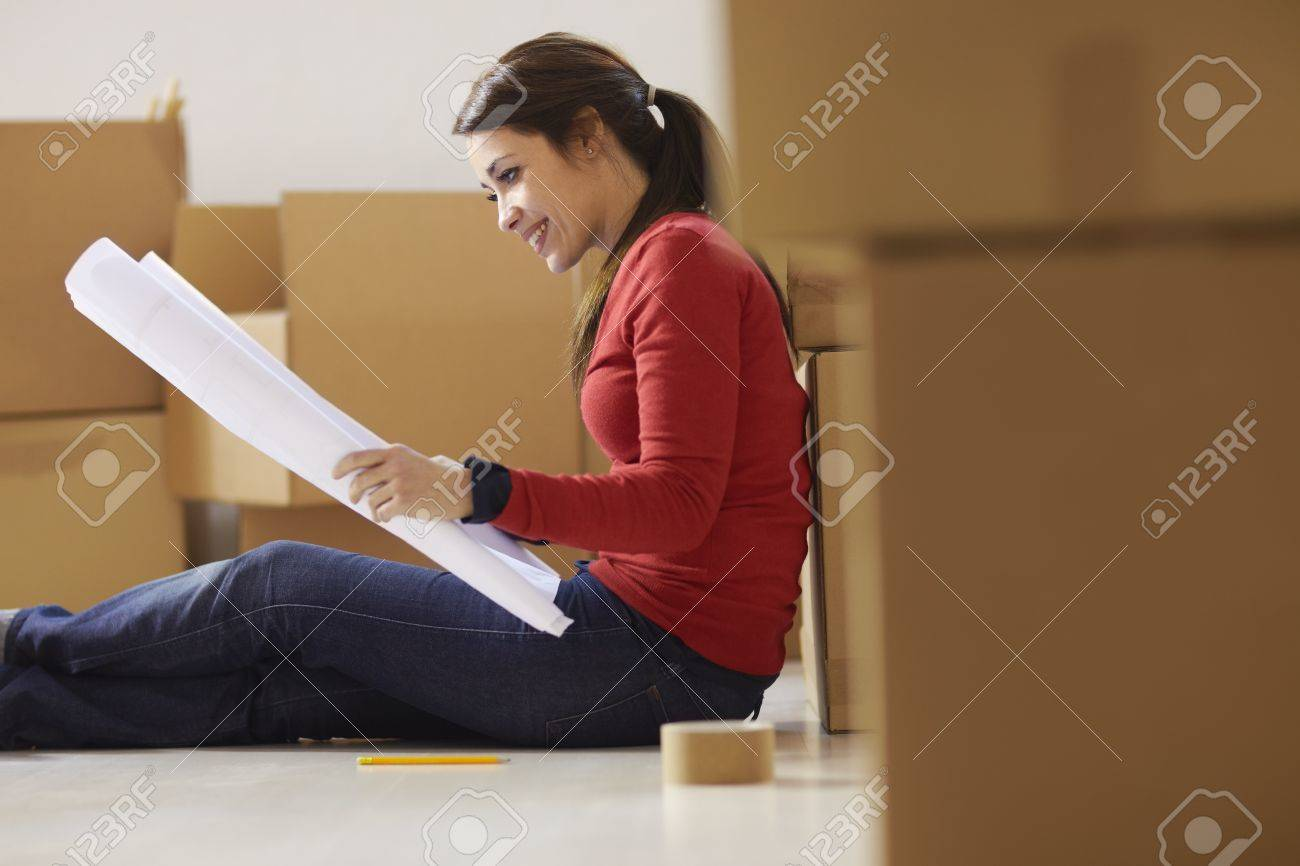 mid adult happy woman moving with boxes at new home and looking at blueprint. Side view, Copy space Stock Photo - 12943248