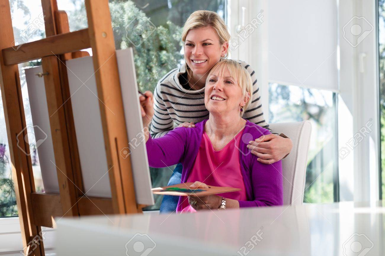Family portrait with happy mother painting for hobby and daughter smiling and hugging her at home Stock Photo - 13408912