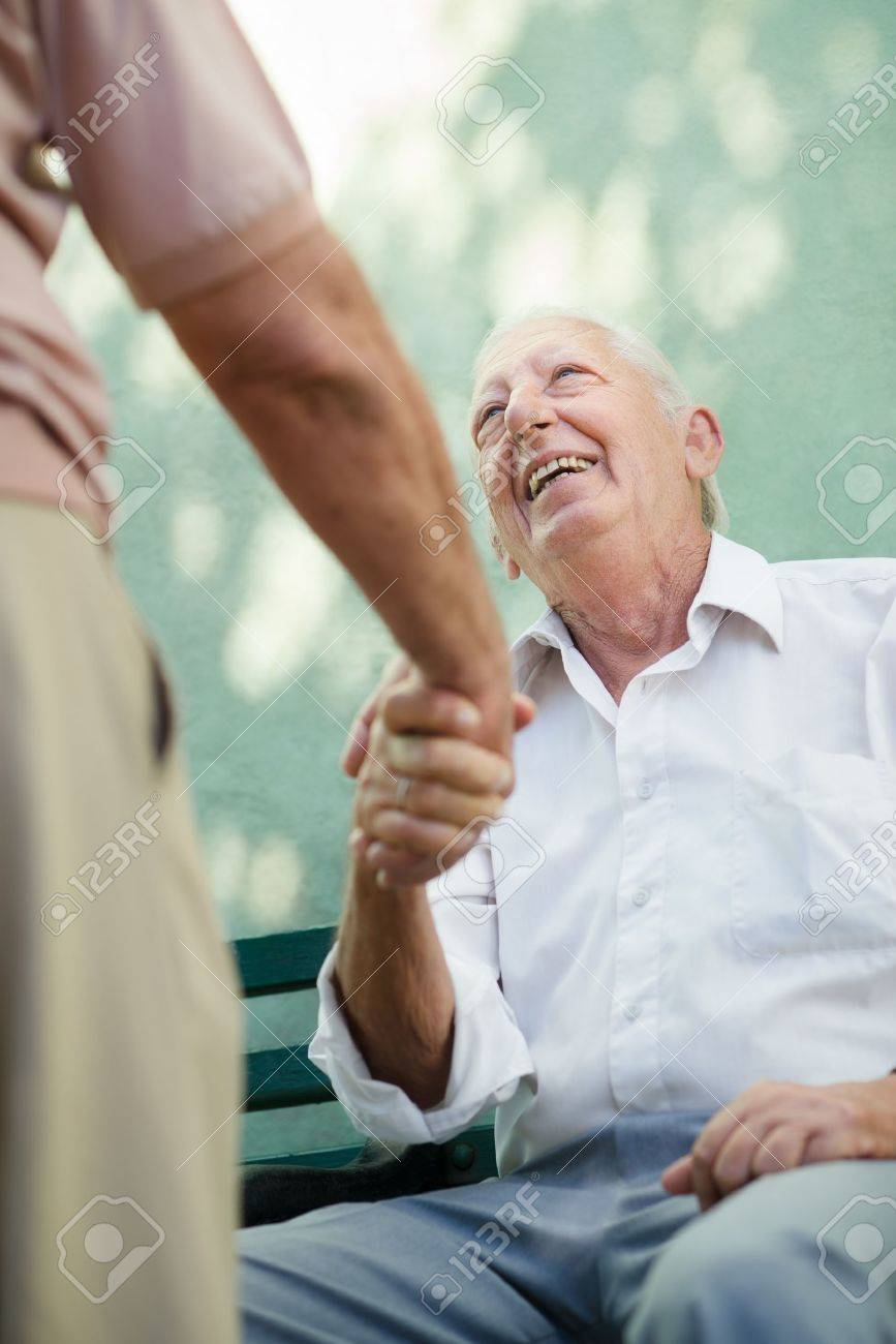 Active retirement, two old male friends talking and shaking hands on bench in public park Stock Photo - 14185615