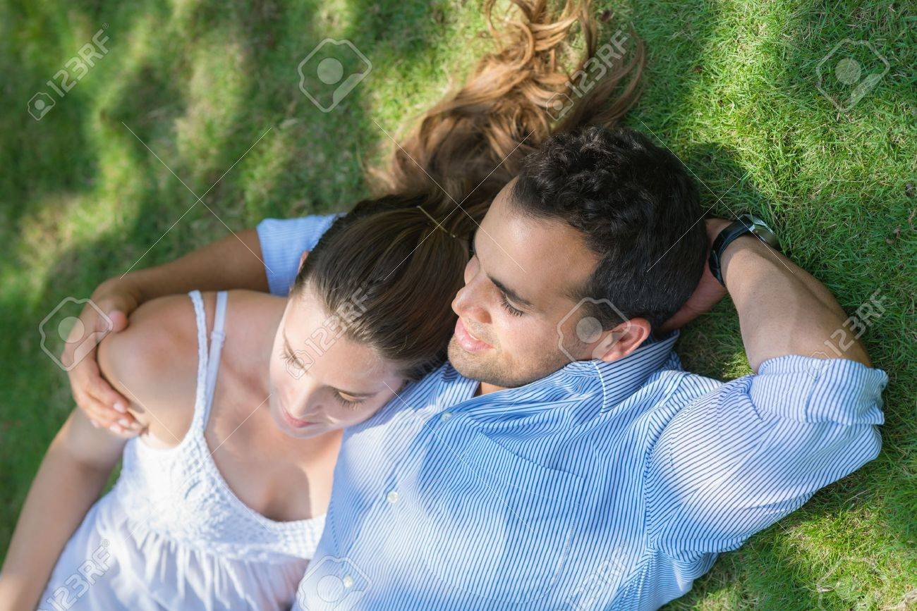 Happy beautiful young man and woman in love, lying on grass in park and relaxing Stock Photo - 14428588