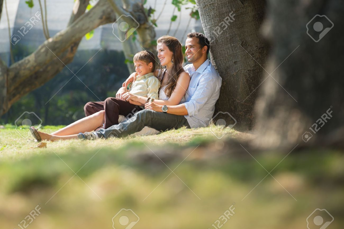 Happy family with man, woman and child leaning on tree in city park. Stock Photo - 14508397