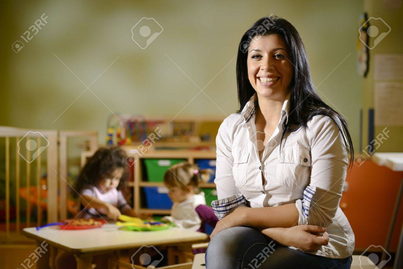 Portrait of female teacher smiling at camera and happy children eating lunch at school. Copy space Stock Photo - 16244074