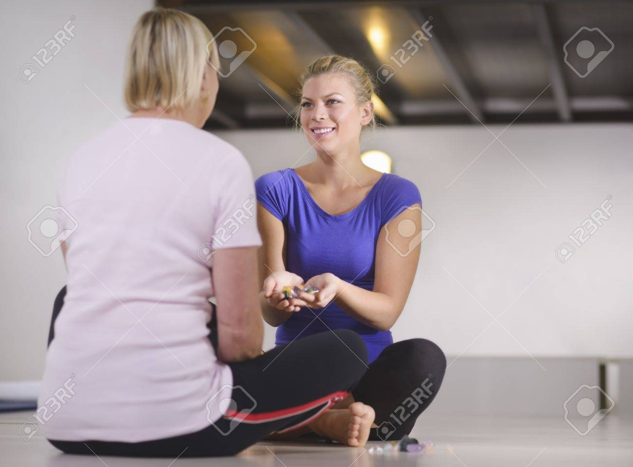 Alternative medicine, pain healing and women, young therapist choosing crystals for reiki therapy with client. Full length, copy space Stock Photo - 16523108