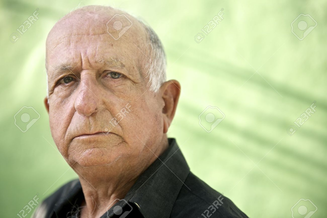 Elderly people and emotions, portrait of serious senior caucasian man looking at camera against green wall Stock Photo - 20054444