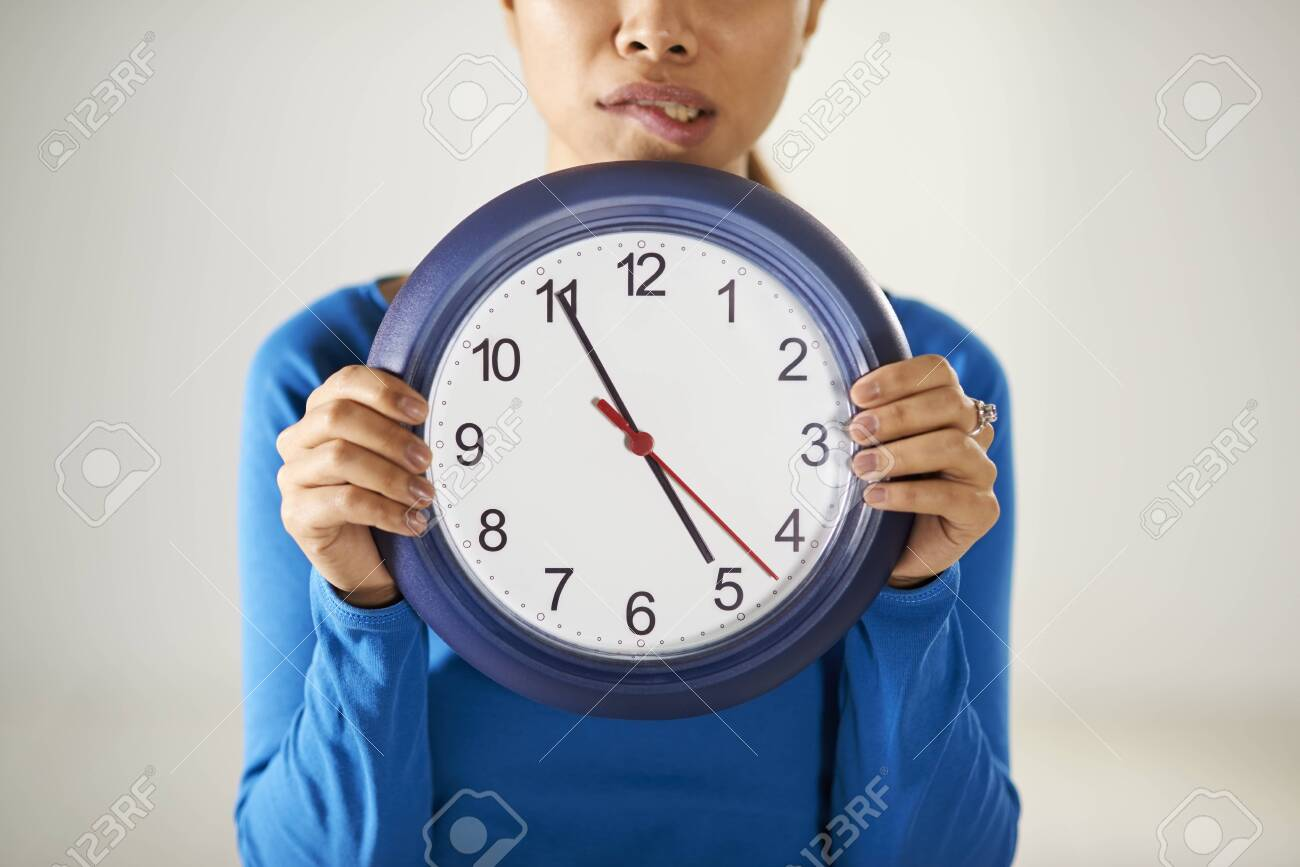 portrait of asian business woman holding big blue watch and looking at camera with worried expression Stock Photo - 26816697