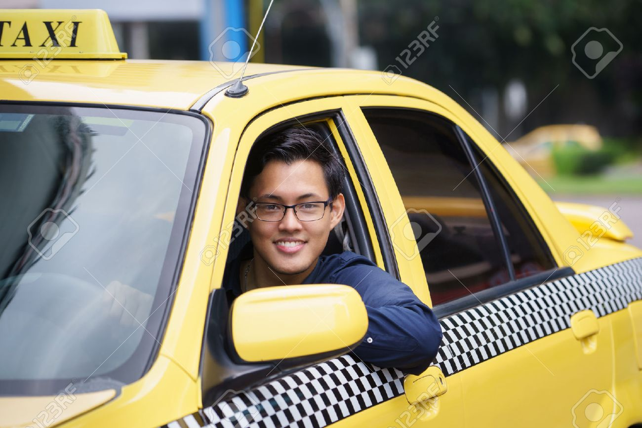 Portrait Of Happy Chinese Taxi Driver In Yellow Car Smiling And Looking At  Camera Stock Photo