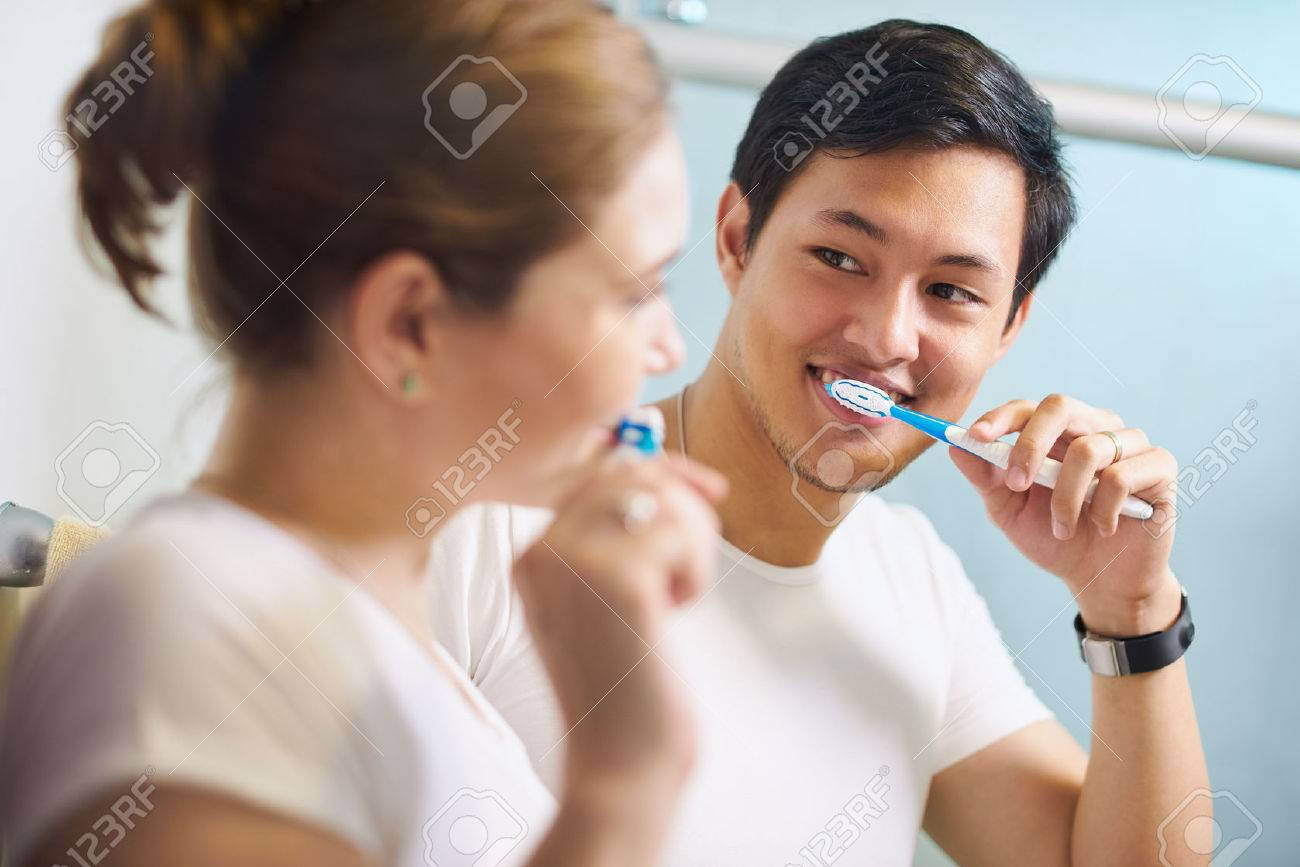 Young couple living together, washing teeth in bathroom in the