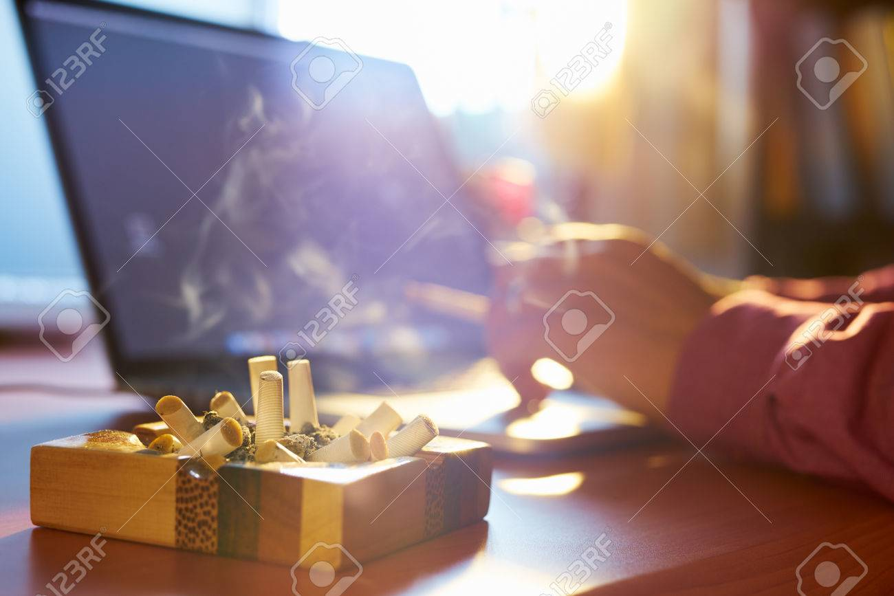 Close up of ashtray full of cigarette, with man in background working on laptop computer and smoking indoors on early morning. Concept of addiction and abuse of nicotine. - 42016233