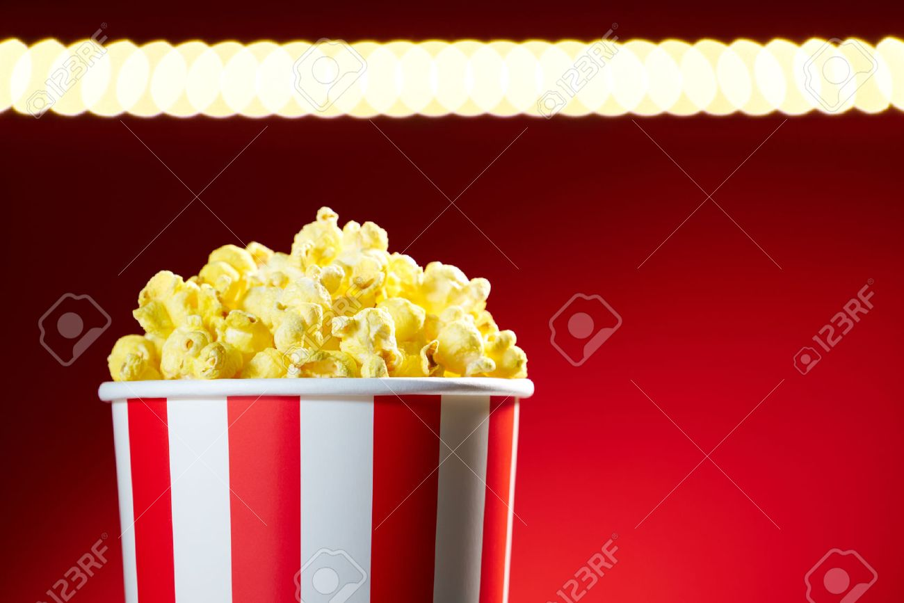 Red bowl full of popcorn on red background for film, TV, television watching. Concept of movie night - 44362347