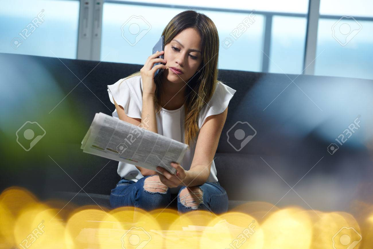 Young unemployed female doing job hunting and reading employment announcements. The girl is sitting on her sofa holding a newspaper and does a phone call to arrange an interview. - 46344687