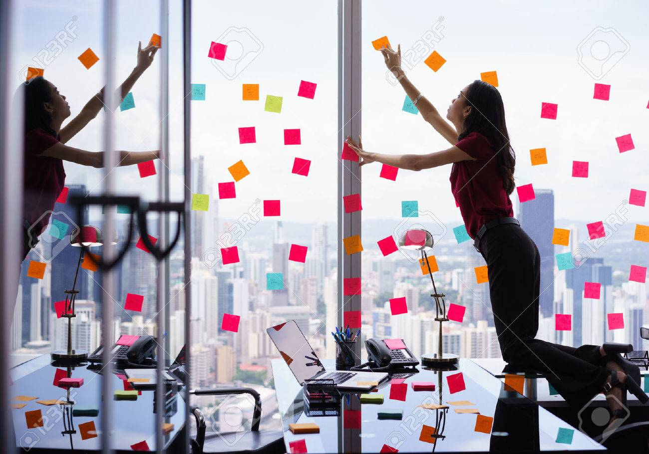 Mixed race secretary working in modern office in skyscraper, sticking adhesive notes with tasks on window. The girl feels stressed and overwhelmed - 51500374