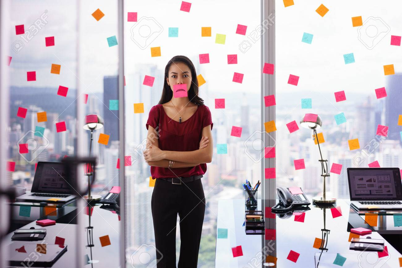 Mixed race woman working in modern office with reminders on skyscraper window. The girl feels stressed, holds a sticking note with sad emoticon on mouth. - 51500377
