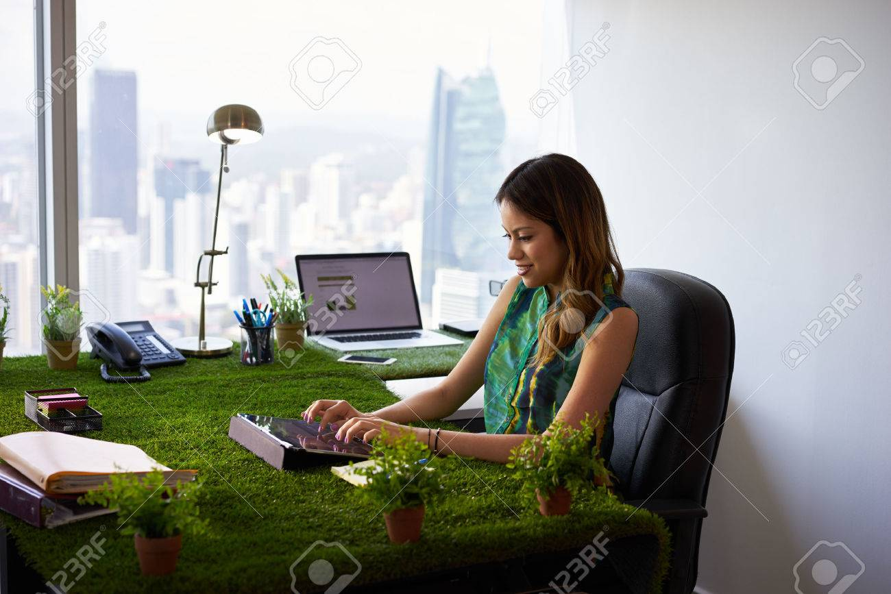 Concept of ecology and environment: Young business woman working in modern office with table covered of grass and plants. She types on tablet pc - 51551646