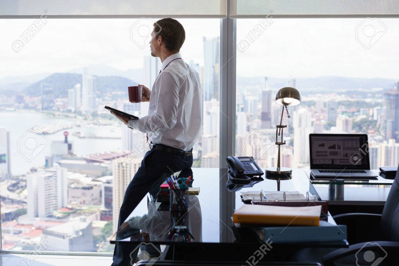 Adult businessman sitting on desk in modern office and reading news on tablet pc with a cup of coffee. The man looks out of the window and contemplates the city and skyscrapers. - 51897130