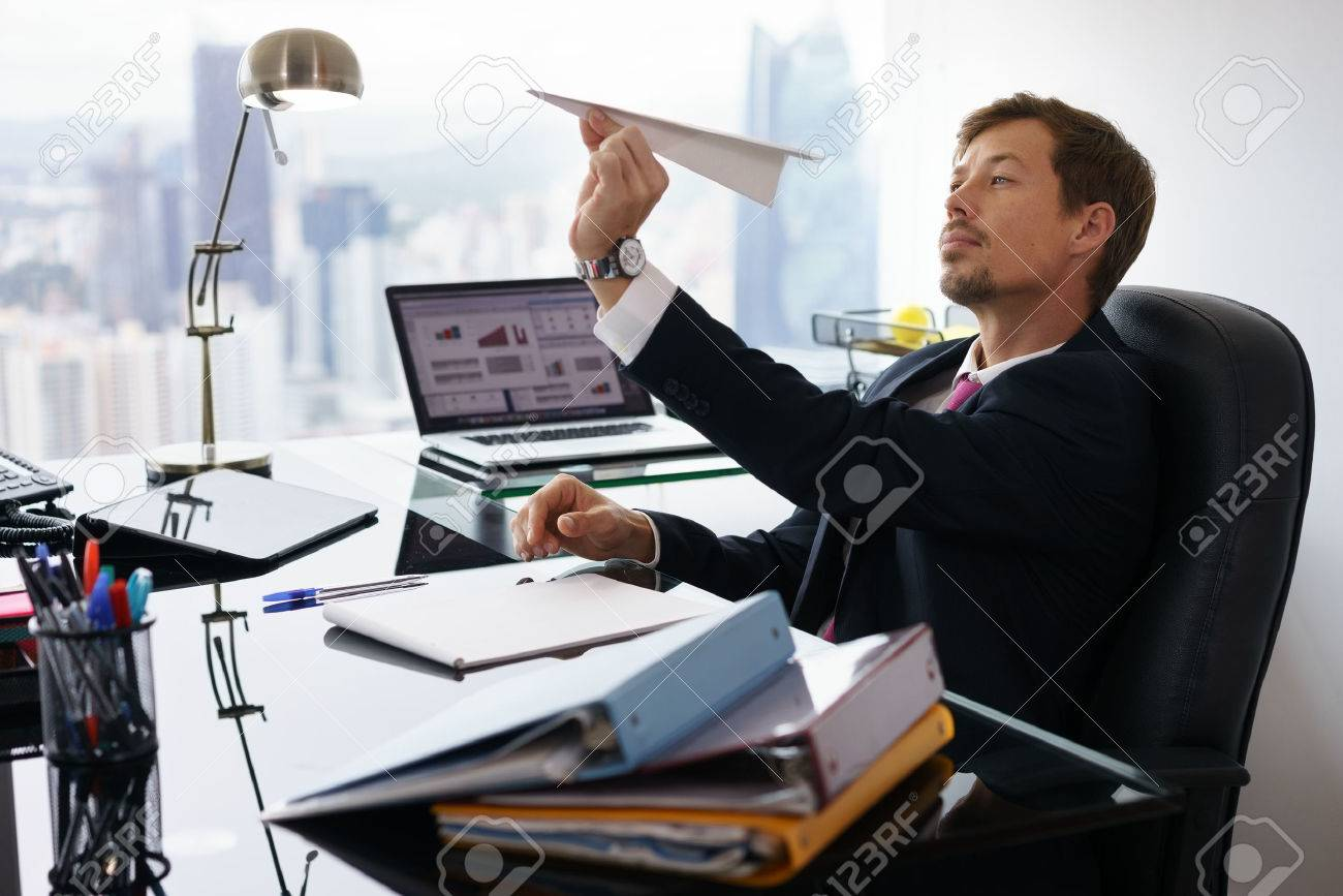 Corporate manager in modern office takes a break and prepares a paper airplane. The bored man dreams of his next vacations and leans back on his chair - 52936172