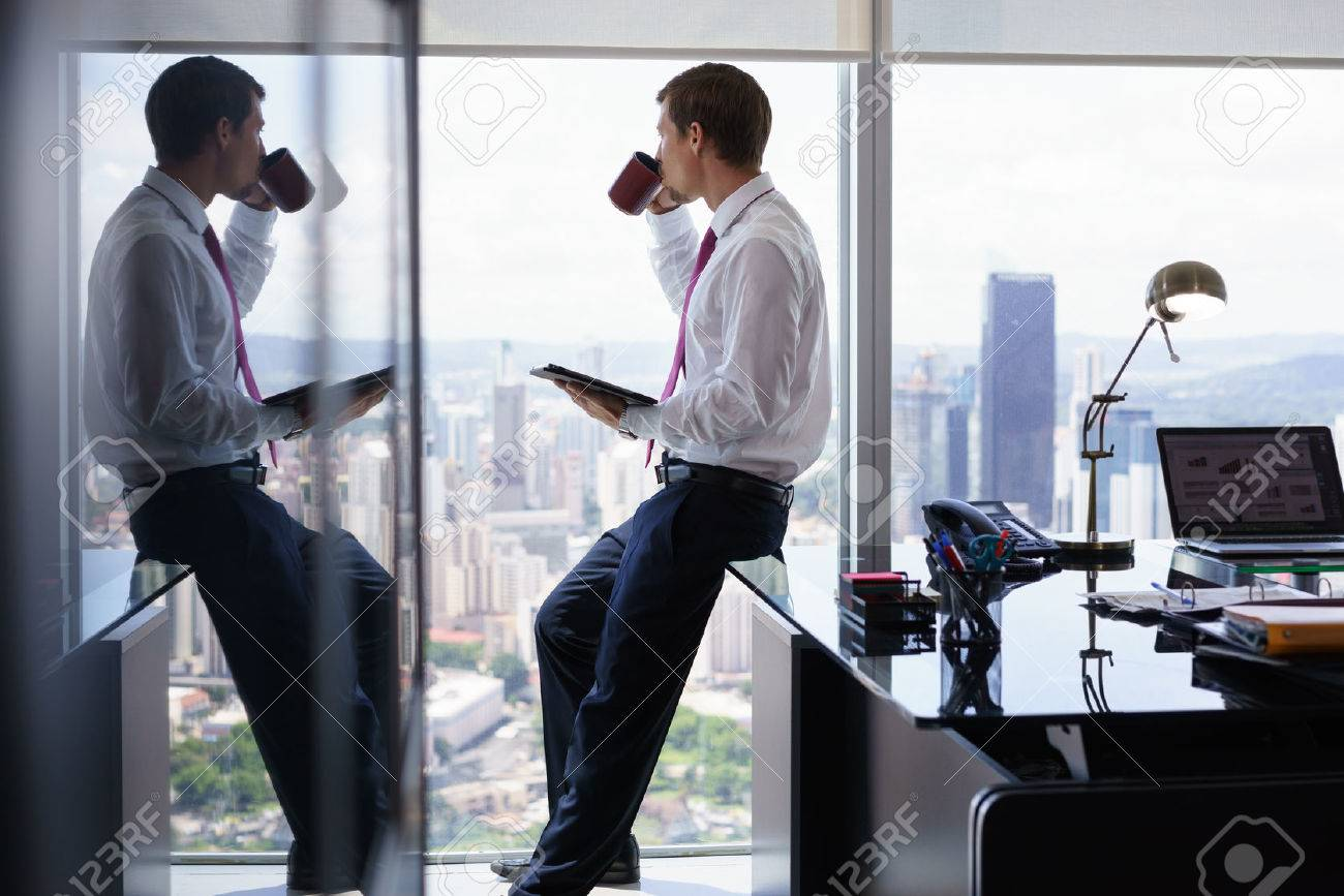 Adult businessman sitting on desk in modern office and reading news on tablet pc with a cup of coffee. The man looks out of the window and contemplates the city and skyscrapers. - 53102515