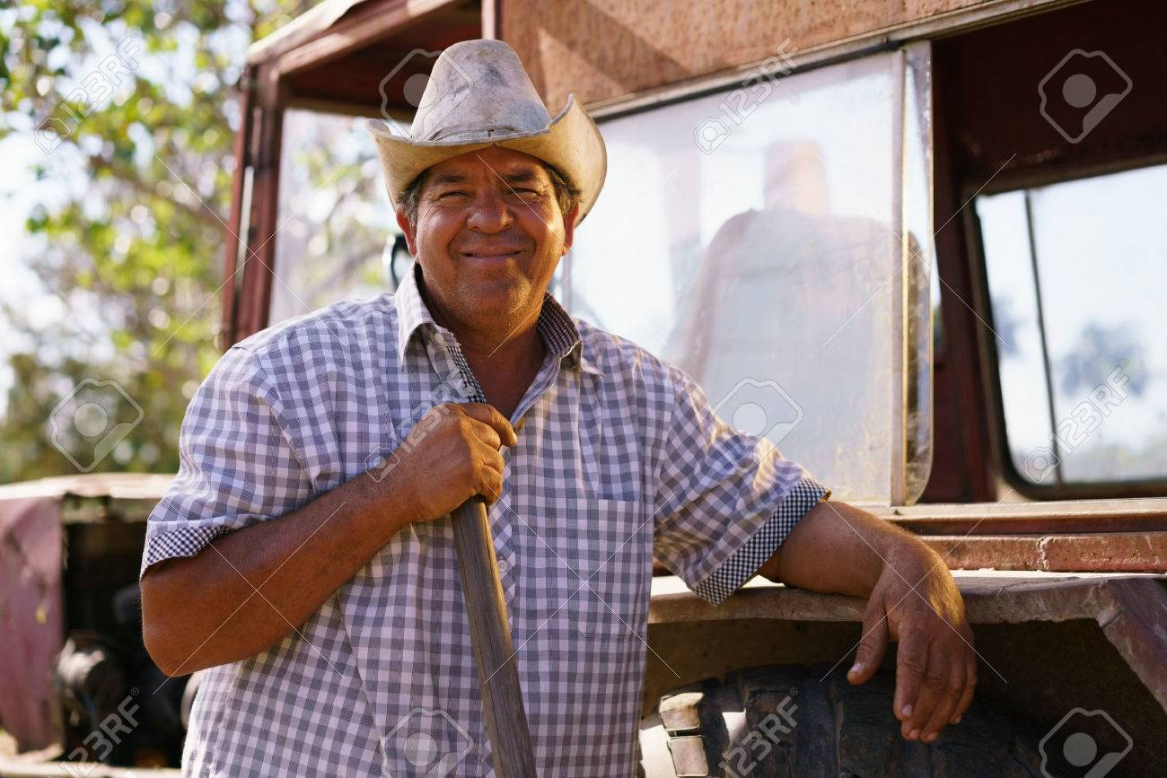 Farming and cultivations in Latin America. Portrait of middle aged hispanic farmer sitting proud in his tractor at sunset, holding the volante. He looks at the camera and smiles happy. - 56140488