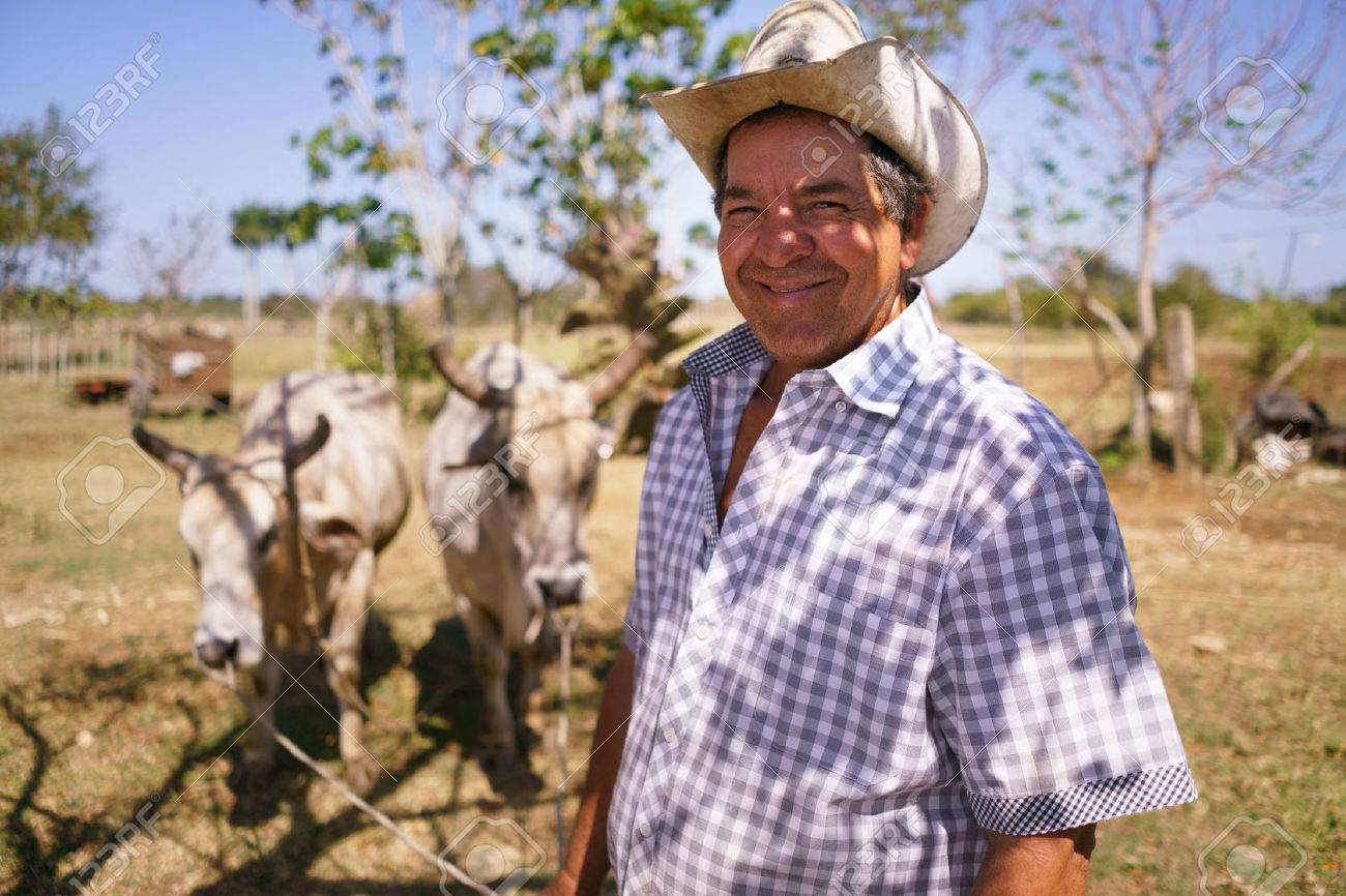 Farming and cultivations in Latin America. Portrait of middle aged hispanic farmer sitting proud in his tractor at sunset, holding the volante. He looks at the camera and smiles happy. - 56140489