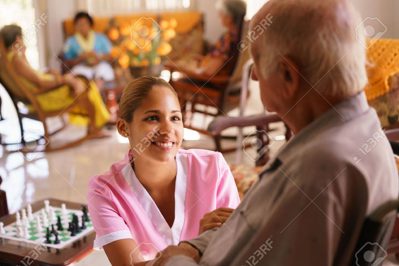 Old people in geriatric hospice: young attractive hispanic woman working as nurse takes care of a senior man on wheelchair. She talks with him then goes away to help other patients - 56097377