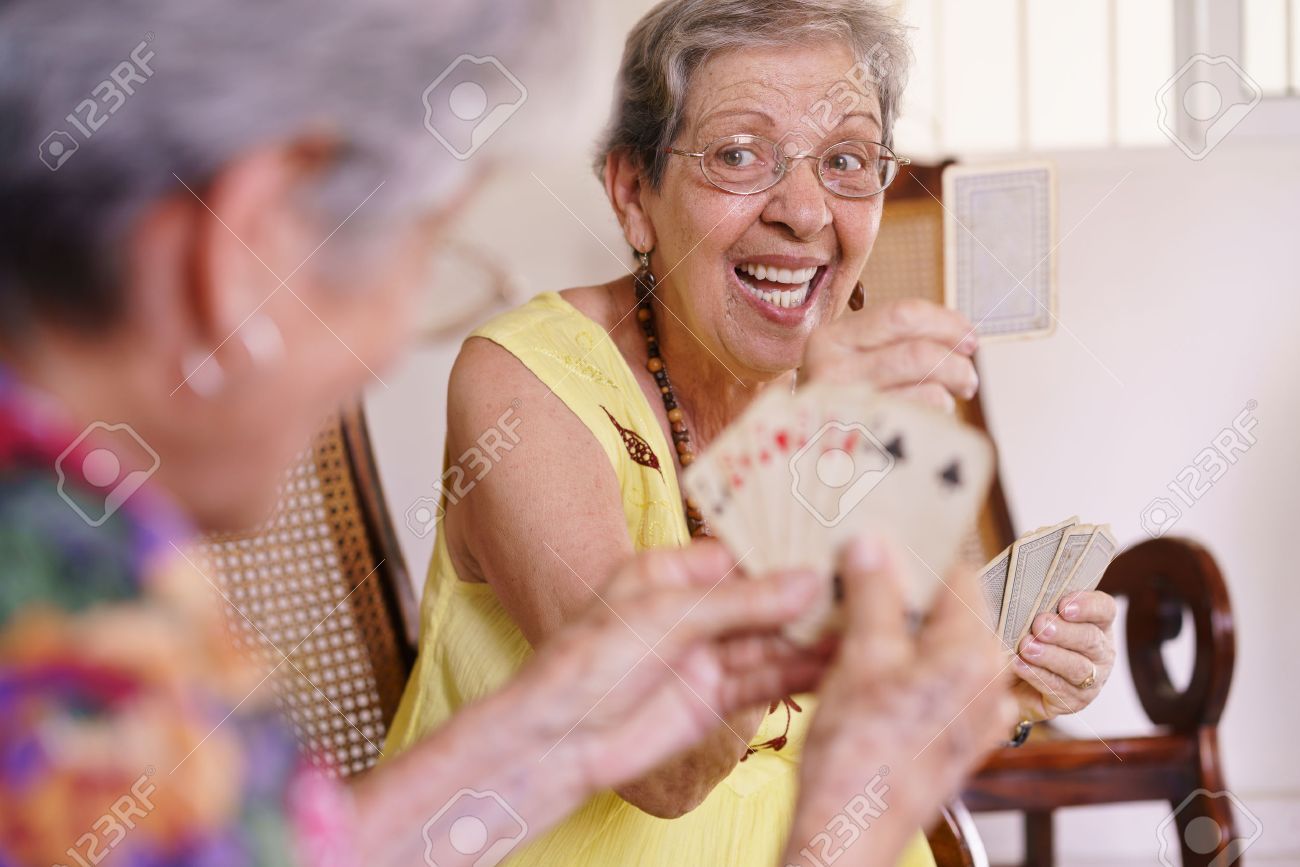 Old people in geriatric hospice: group of senior women playing cards and having fun together. An aged lady wins the game and shows a card to her rival - 56097386