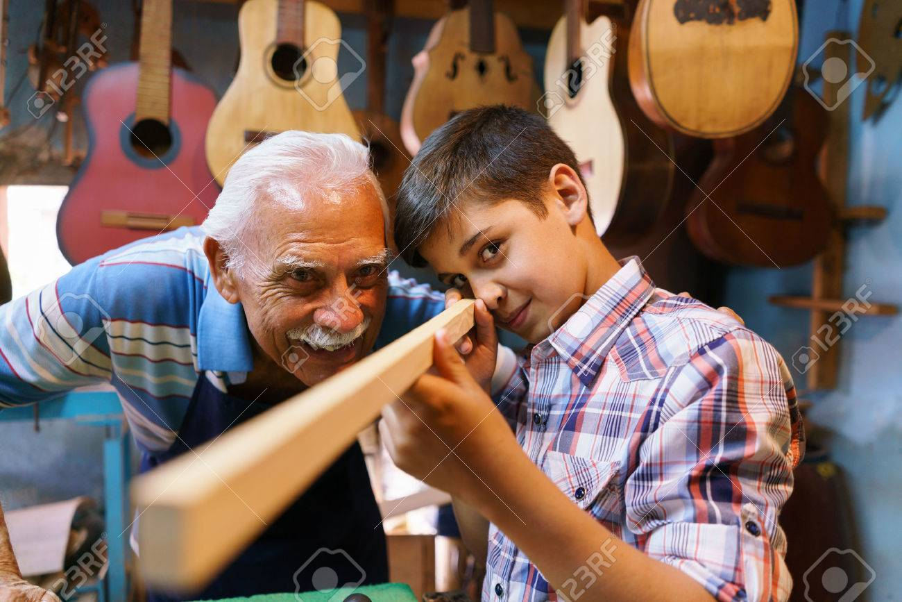 Small family business and traditions: old grandpa with grandson in lute maker shop. The senior artisan teaches to the boy how to chisel wood to make a music instrument. The kid looks carefully at his work - 56097405
