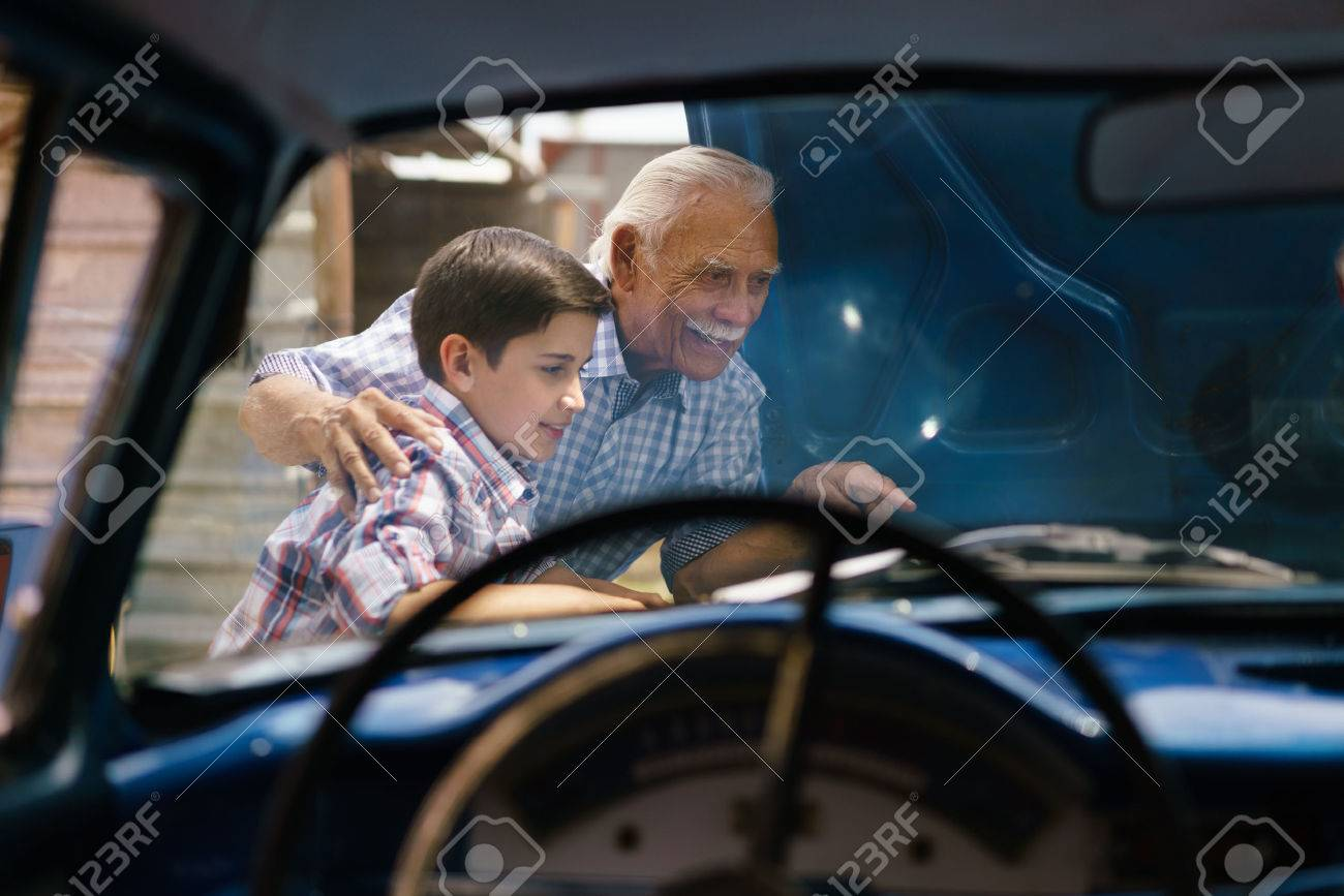 Family and Generation gap. Old grandpa spending time with his grandson. The senior man shows the engine of a vintage car from the 60s to the preteen child. They smile happy. Viewed from the interior of the car - 56097407