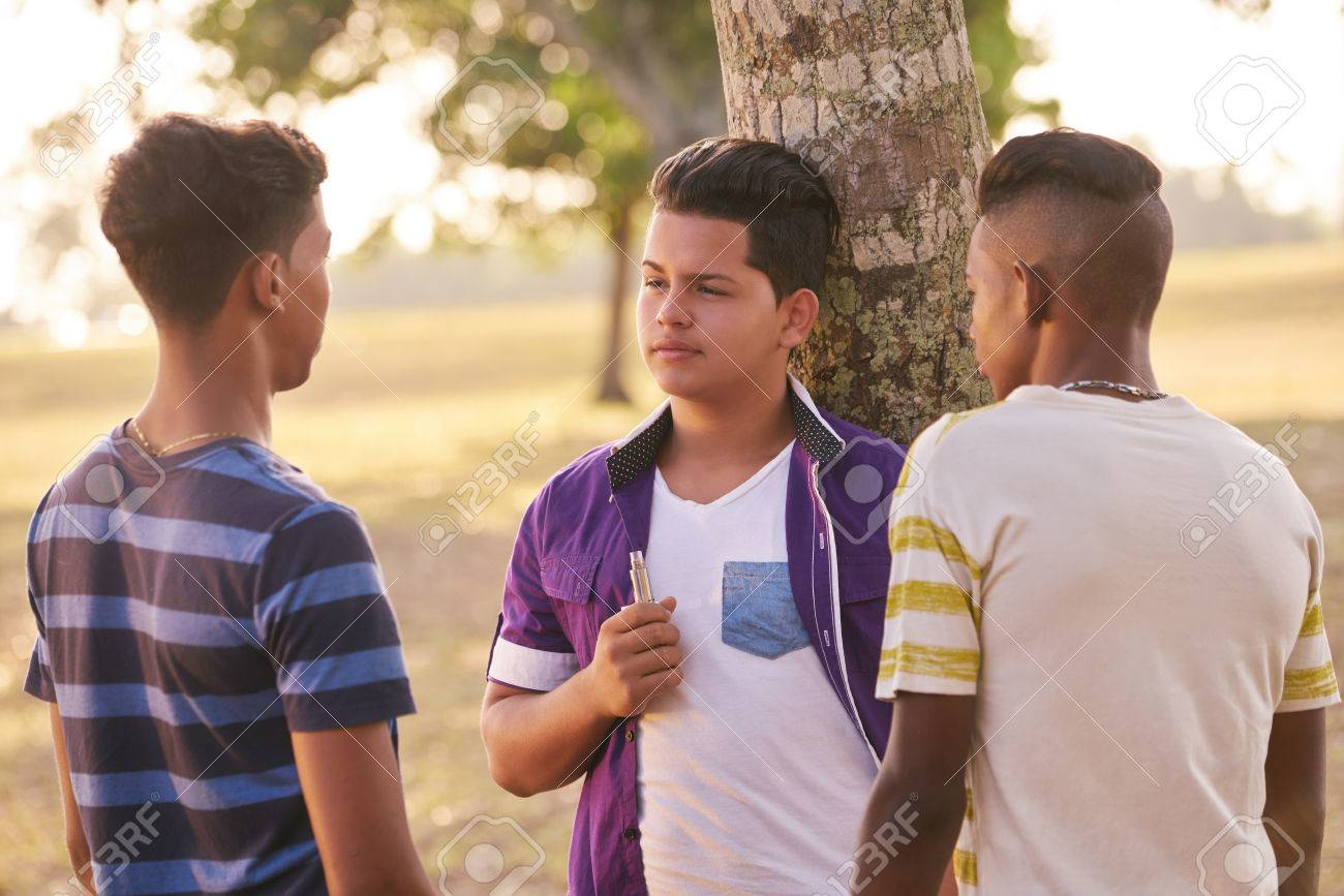 Youth culture, young people, group of male friends, multi-ethnic teens outdoors, multiracial boys together in park. Kids smoking electronic cigarette, e-cig smokers. Health problems, social issues - 58998782