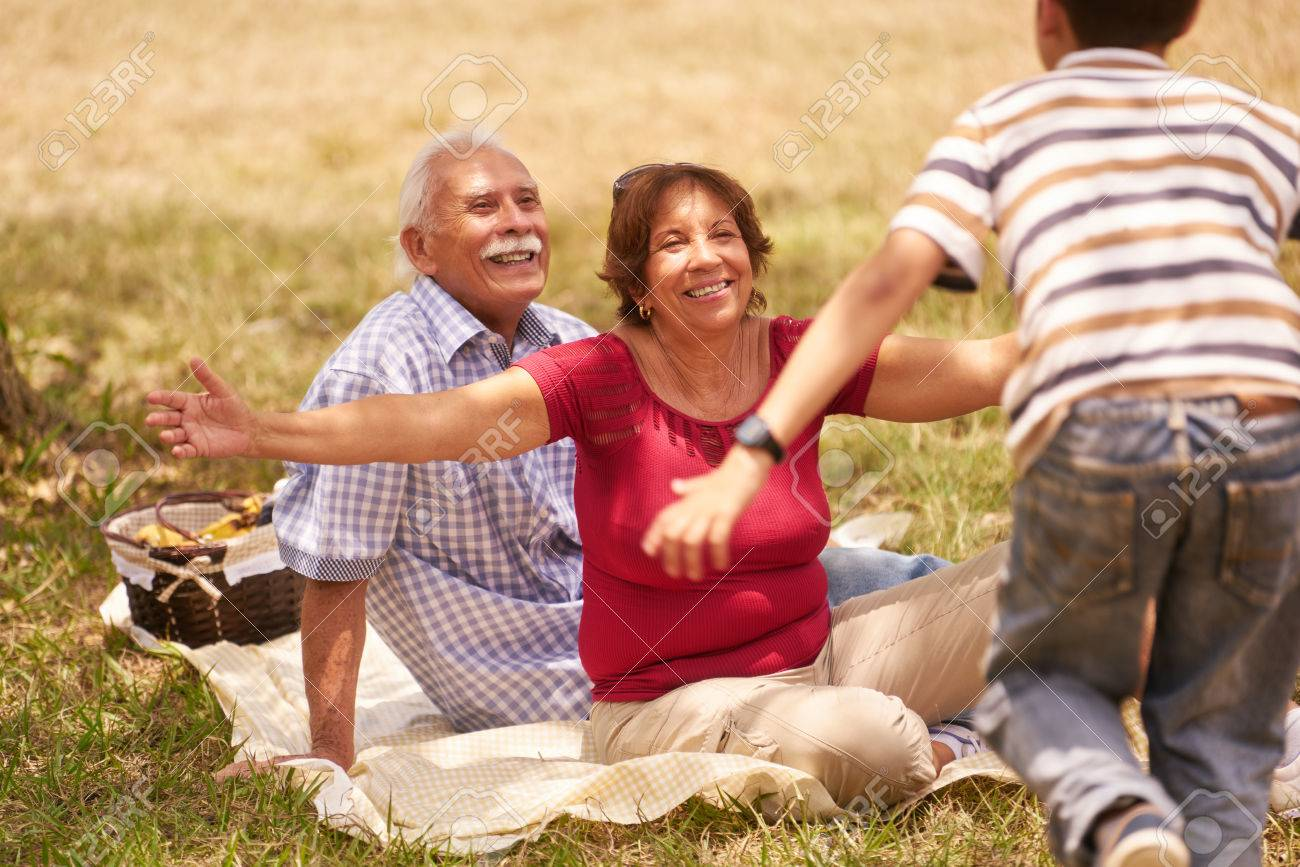 Old people, senior couple, elderly man and woman. Outdoor family having fun with happy grandpa and grandma hugging boy at picnic in park. - 60028149