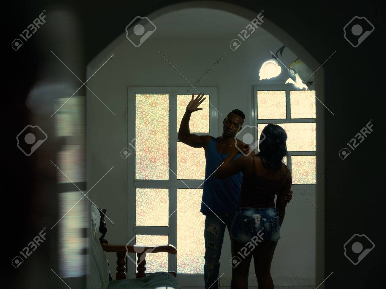 Social issues, aggression and violence on women, alcoholic black man hitting and beating woman at home. Domestic fight with aggressive husband and abused wife crying - 72344313