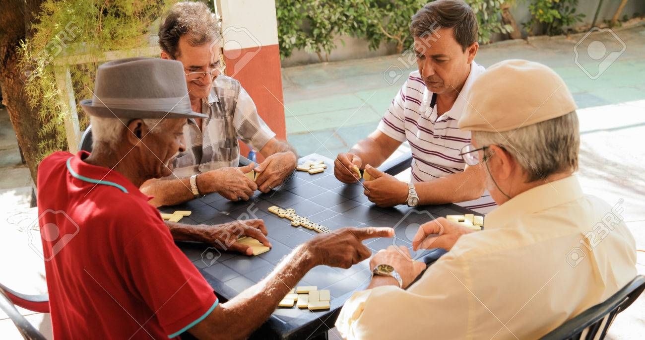 Retired people, seniors and free time. Old latino men having fun and playing game of domino in Cuba. - 82752065