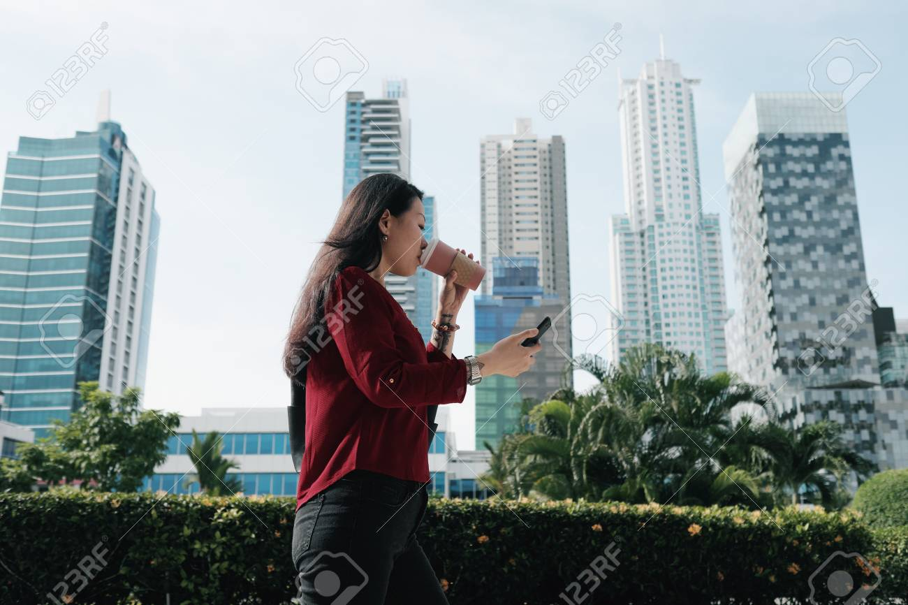 Chinese Woman With Phone Walking And Drinking Coffee - 108417261