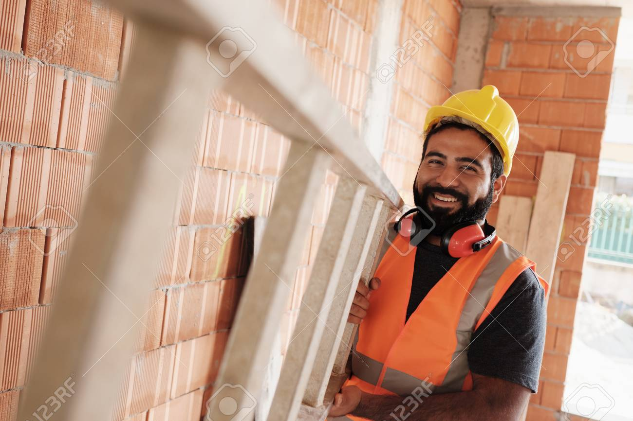 Portrait Of Happy Hispanic Worker Smiling In Construction Site - 121113668