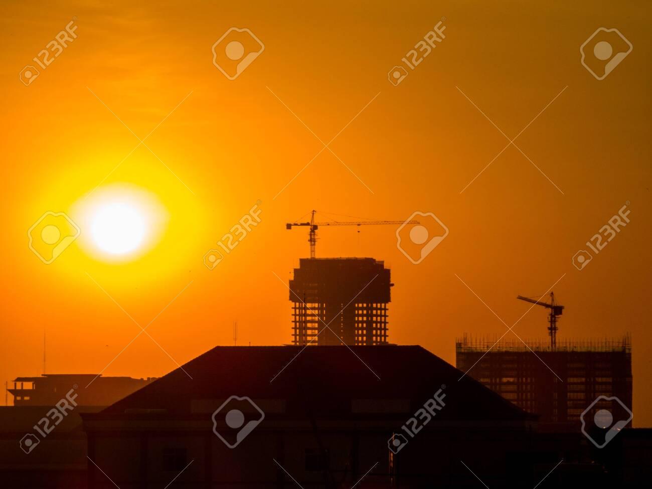 Construction cranes at sunset. In Phnom Penh, Cambodia - 151513378