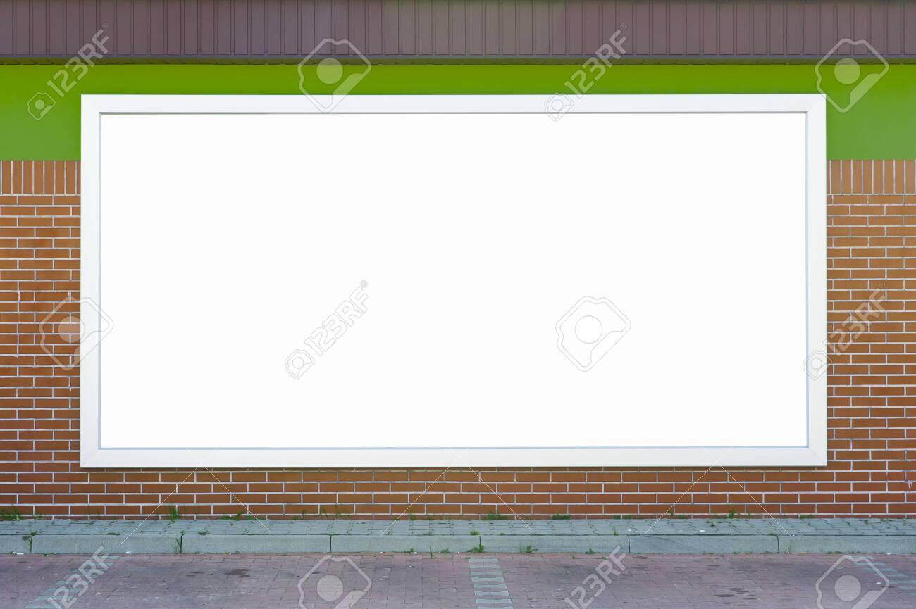 Blank billboard mounted on the brick wall. - 144061740